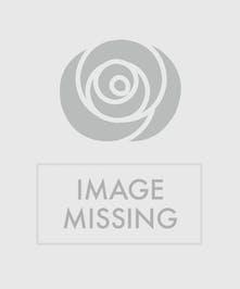 A lovely combination of garden roses, ranunculus, pink spruce, waxflower, and assorted greens are served on a cake plate.