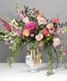 Akita roses, Cloony ranunculus, dendrobium orchids, Carpe Diem roses, peonies, snapdragons, lisianthus and premium greenery in an elegant vase