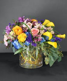 Yellow,peach,pink roses, yellow calla lilies, blue hydrangea, white/pink alstroemeria, purple statice, fragrant waxflower, and seeded eucalyptus.