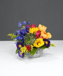 Colorful arrangement of sunflowers, orange roses, purple aster, hot pink spray roses, and a popular succulent tucked in the blooms.