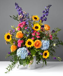Boldly colored bouquet abloom with orange roses, petite sunflowers, purple lisianthus, hot pink spray roses