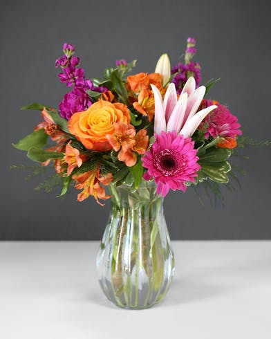 A glass vase includes roses, lilies, gerbera daisies in vivid shades of orange and hot pink.