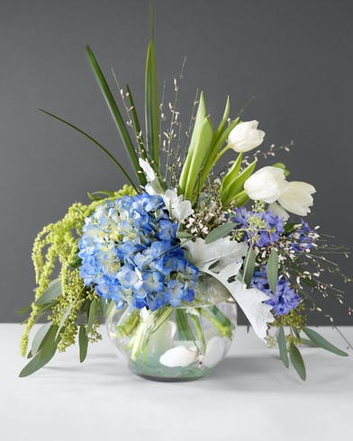 White ginestra, blue hydrangea, light green hanging amaranthus, blue hyacinth, white tulips, lily grass, dusty miller, Eucalyptus, Seafoam glass, shells in a clear glass bowl.