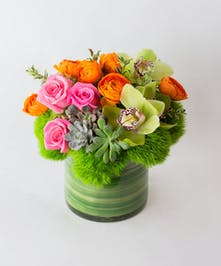 Cymbidium orchids, orange ranunculus, pink roses, green dianthus and succulents, brought together in a leaf lined, modern pave style vase.