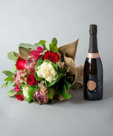 wine and flowers, flowers and wine, wine, flowers, sweet wine, wrapped flowers, flower wrap, protea, roses, red roses, kale, magnolia, magnolia leaves, wax flower, eucalyptus