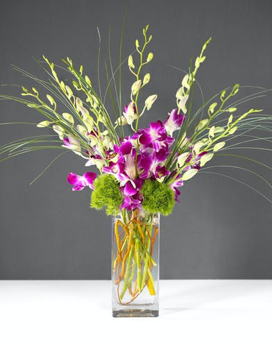 This arrangement includes stunning dendrobium orchids in a vase with exotic greenery.