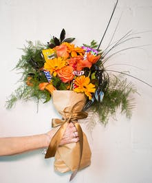 Orange Gerber daisies, roses, tulips, calla lilies and black greenery (plus four candy barst) tied together with a chocolate brown ribbon