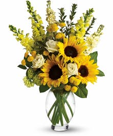 Yellow bouquet of sunflowers, roses, snapdragons, stock, and mums in a glass vase.
