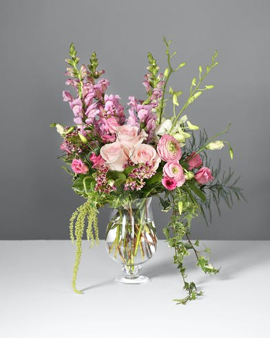 Akito roses, Clooney ranunculus, lisianthus, lavender snapdragons, white dendrobium orchids, hanging amaranthus, and assorted greenery