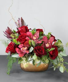 The Garnet Glam arrangement features burgundy cymbidium orchids, seeded eucalyptus, black magic roses and safari sunset for vibrant color.