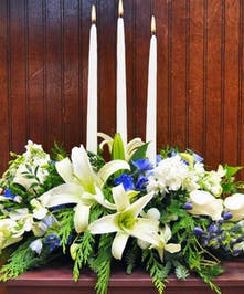 A classic centerpiece of white lilies, blue delphinium, white orchids, white roses, and more ready to shine at your Hanukkah gathering!