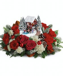 An instant Christmas classic, this festive arrangement of red roses and fresh winter greens