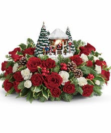 This festive arrangement of red roses, white carnations and fresh winter greens is hand-delivered with a delightful Thomas Kinkade sculpture!